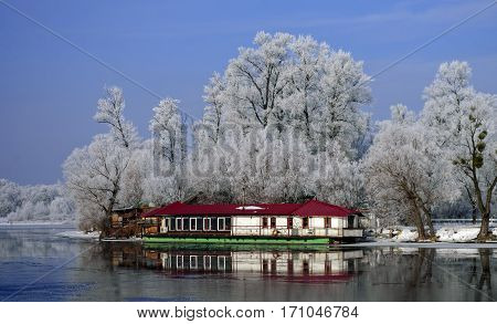 Temporary structure of white under the red roof near the river shore of the water under the big trees in the frost frosty morning under a blue sky.