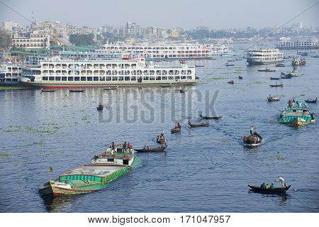 DHAKA, BANGLADESH - FEBRUARY 21, 2014: Residents of Dhaka cross Buriganga river by boats in Dhaka, Bangladesh. Thousands of people in one of the most populated capitals of the world use ferry boats daily on the way to work and back home.
