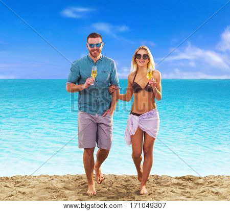 young couple on tropical beach walking drinking champagne.