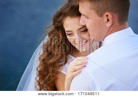 bride and groom embracing at the lake for a walk.