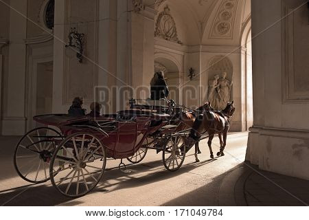 Traditional horse riding in a horse-drawn Fiaker through the gateway of Michaelertrakt in the Inner City of Vienna, Austria.