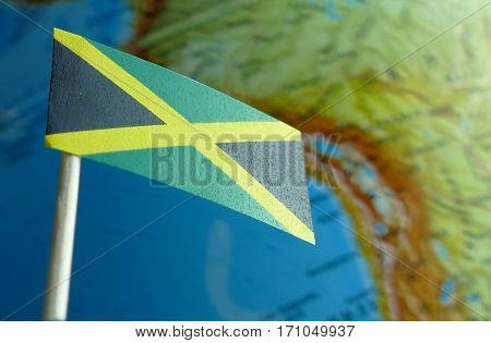 Jamaica Flag With A Globe Map As A Background Macro