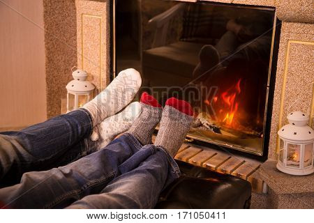 Legs of couple in woolen socks heat up near cozy fireplace, warm toned image