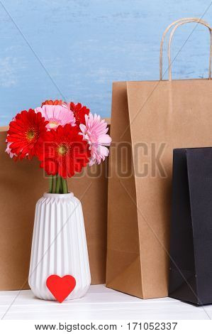 Mockup of blank shopping bags. Gerbera flowers and red heart. Brown and black craft packages. Concept for sales or discounts. Blue wooden rustic board.