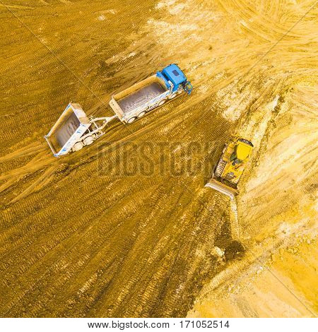 Aerial view of a working bulldozer and truck ion a construction site. Industrial background and heavy industry from above.