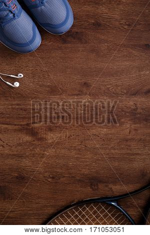 Fitness gym equipment. Tennis racquet. Sneakers, music headphones and towel. Workout footwear. Grunge rustic wood background.