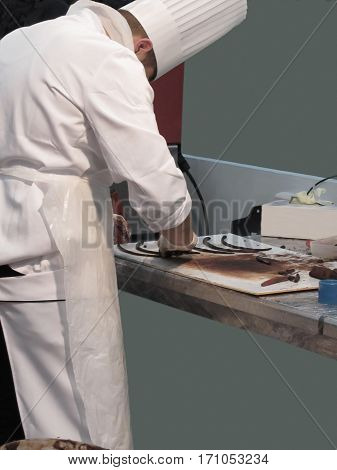 Pastry chef in the kitchen preparing chocolate decoration on a worktop