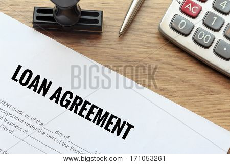 Loan agreement document with rubber stamp and calculator on wooden desk
