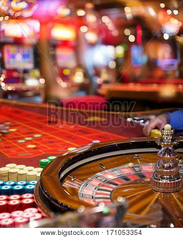 Casino - Roulette In Motion With Blurred Slot In Background