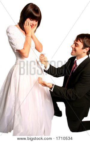 Handsome Groom With A Proposal For Marriage And A Beautiful Shocked Bride In Her Bridal Dress Lookin