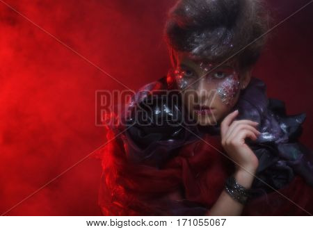 Portrait of young stylisn woman with creative visage over red background.