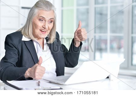 excited senior woman using laptop and showing thumbs up