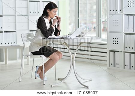 young brunette woman working at office, using laptop
