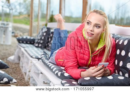 Attractive young blonde woman typing on phone on terrace . Sunny morning, relaxing time