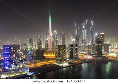 Skyline of Dubai downtown at night. Burj Khalifa illuminated in national colors of the UAE - green red and white. United Arab Emirates Middle East