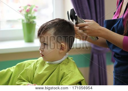 Barber cutting hair with clipper isolated on white background.