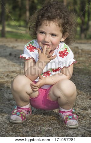 In the summer in the woods a little funny girl sat down and holds a finger in his mouth.