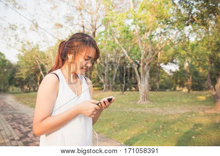 Happy sporty woman wearing smartphone armband and earphones before running in autumn. Female athlete listening music during fitness training outdoor. Vintage effect style pictures.