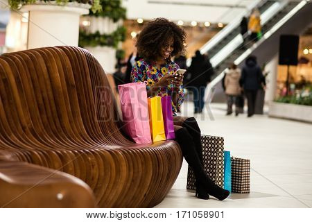 Curly haired afro-american girl in a shopping mall sitting on a bench with the mobile phone in herhends