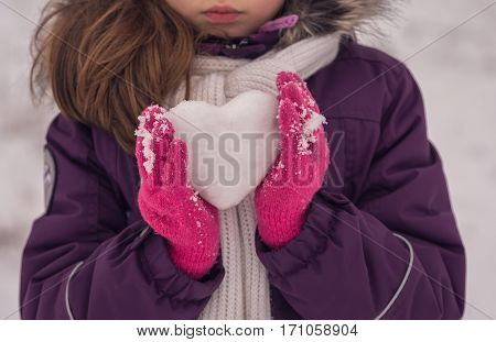 Girl lovingly gives icy heart. Happy Valentine's day.