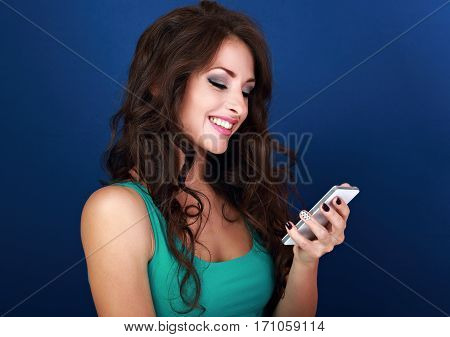Happy Natural Emotion Woman Texting The Sms On Mobile Phone On Blue Background And Looking On It. Cl