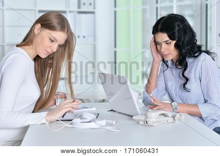 two young girls working at office using laptop