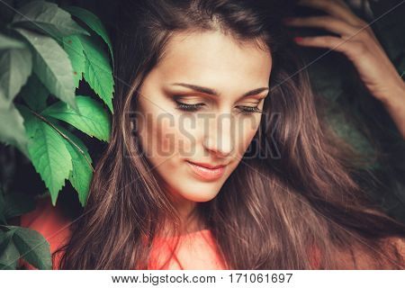 Happy beautiful young woman in spring blossom park. Pretty Girl with Spring Flowers. Fashion Model Outdoors