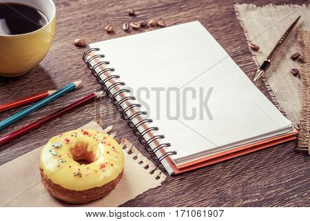 Opened notepad and cup of coffee with donut on wooden table