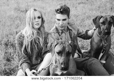 Two Rhodesian ridgeback in a field on a leash in men and women. Young man and woman sitting on the grass on the background of wood. Love story. Fashion photography concept. Young man in trenchcoat girl in a sweater and a skirt. Boy and girl walking with a