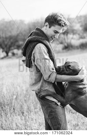 man playing with dog in the field. Fashion photo concept. Rhodesian ridgeback