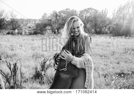 Girl playing with a dog in the field. Blonde woman. Fashion photo concept. Rhodesian ridgeback
