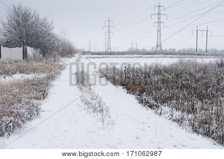 Country landscape with an earth road near high-voltage lines after hoar-frost attack