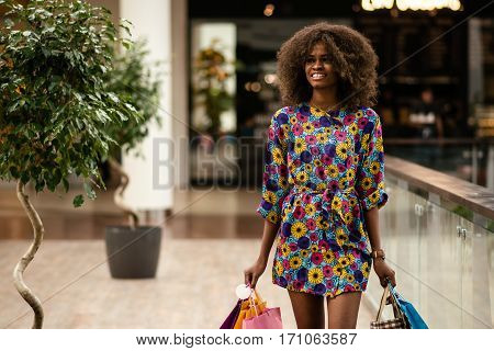 Pretty afro-american girl in a shopping mall. Curly haired and smiled girl.