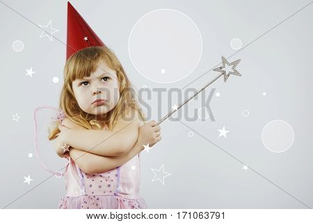 Upset girl, with curly blond hair, wearing on pink dress, red festal hat and fairy wings on her back, posing with silver magic stick, on gray background with white stars, in studio, waist up
