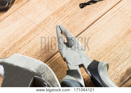 Drill pliers screwdriver tools on wooden table