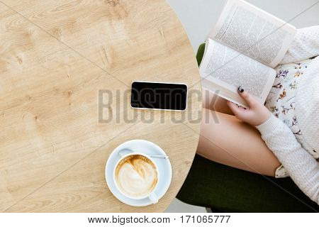 Woman's hands with black manicure holding opened book, cup of coffee and mobile phone  on light wooden table, flat lay, mock up, point of view.
