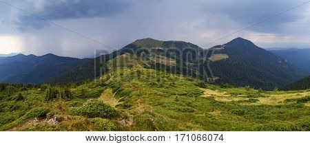Panoramic view on high mountains and stormy sky with clouds is opened from the green marvelous lawn.