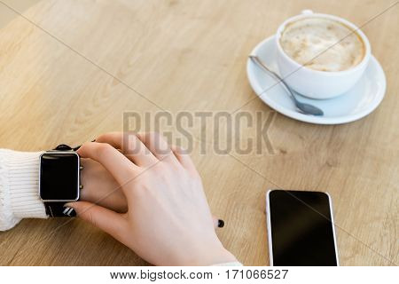 Woman's hands wearing white sweater and touching smart watch on hand, mobile phone, cup of coffee on light wooden table, mock up, close up, copy space.