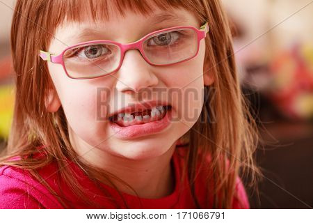 Eyeglasses vision milk teeth falling out eye problems concept. Closeup face of young toddler girl wearing pink glasses for kids without two baby teeth.