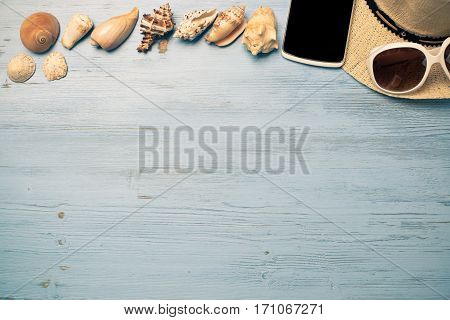 Straw hat sunglasses smartphone among sea shells and stones on wooden surface