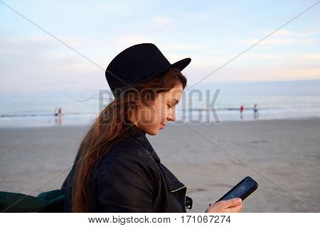 Woman In Hat Holding Cell Phone And Walking On Beach