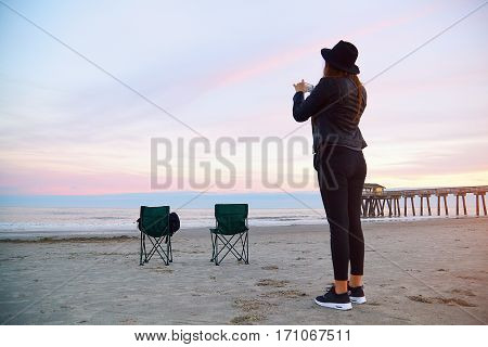 Woman Making Photo By Phone On The Beach On Sunset