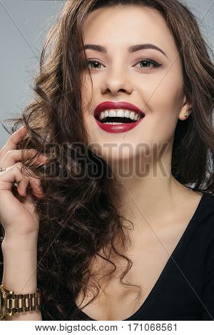 Lovely brunette woman with long curly hair and big eyes wearing black shirt looking at camera, gray studio background, make up model, laughing.