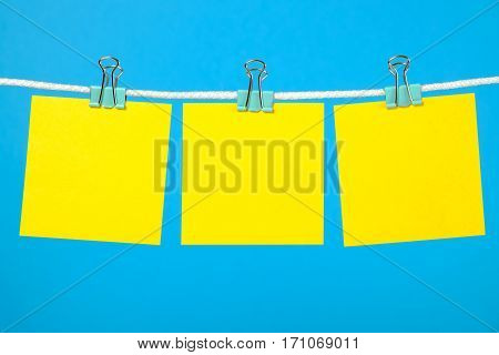Blank yellow paper notes on clothesline over blue background