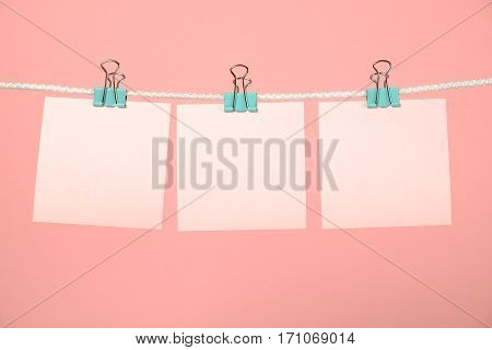 Blank pink paper sheets hanging on string over pink background