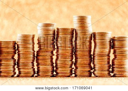 Stacks of golden coins arranged as a graph on glitter background. Financial concept