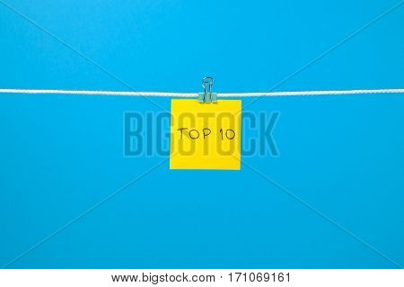 """Yellow Paper Sheet On The String With Text """"top 10"""""""