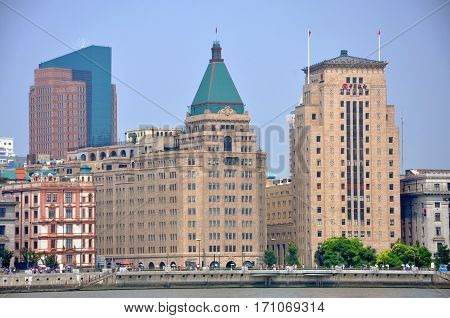 SHANGHAI - AUG. 13, 2012: Fairmont Peace Hotel and Bank of China in the Bund, Shanghai, China. Fairmont Peace Hotel (Green triangle roof) is the most distinctive building was built in 1930. Bank of China (on the right) was built in 1920 with the American