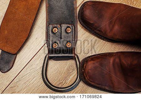 Pair of boots and leather belt in wooden background