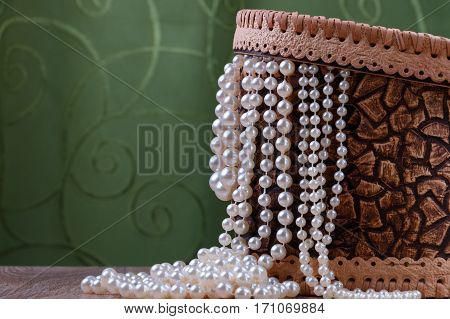 birch bark box with pearl beads on green fabric background
